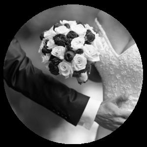 Das Brautpaar mit Brautstrauß, der Bräutigam legt seine Hand um die Braut